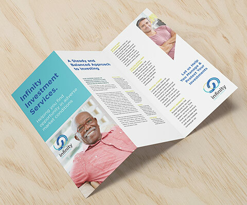 An Infinity Financial Services investment tri-fold brochure laid out on a wood background. The images in the brochure are of an older black man smiling and a younger white male crossing his arms and smiling.