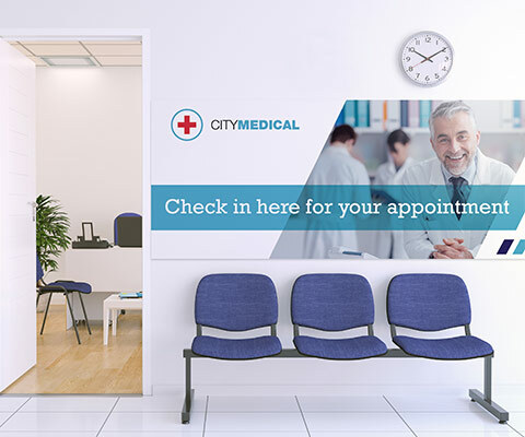 """A large wall sign for City Medical with a smiling doctor. The text reads """"Check in here for your appointment."""""""