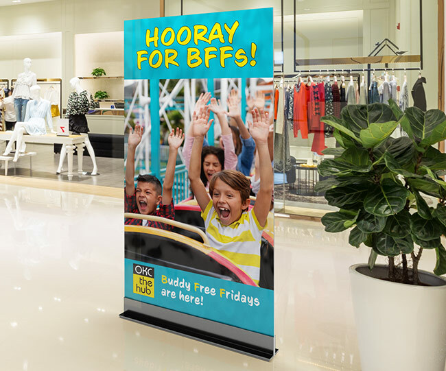 "A tall sign that says ""hooray for BFFs"" and an image of kids on a roller coaster. The sign is sitting in the middle of a mall with a clothing store behind it and a plant to the right of it."