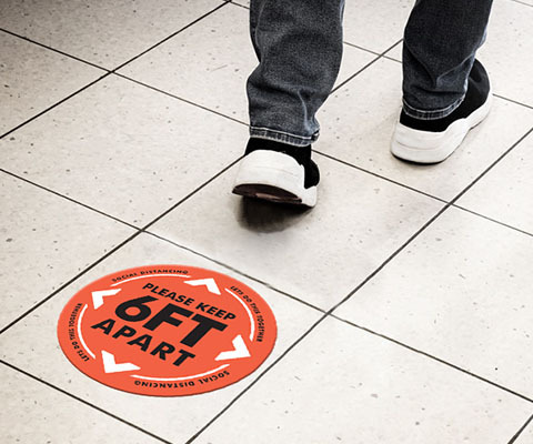 "A circular red floor decal that reads ""Please keep 6ft apart"" with arrows with the feet of a person walking by."