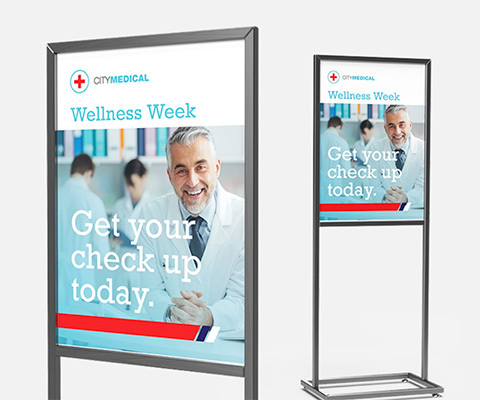 "Two metal display stands with a poster that reads ""City Medical Wellness Week. Get your check up today."""