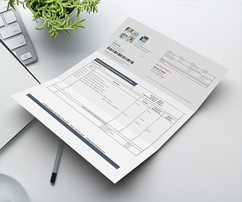 paper invoice sitting on a desk with a pen under it and plant and laptop to the left side