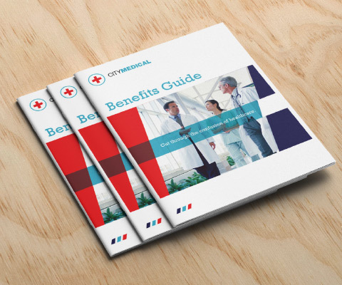 Three Benefits Guides for City Medical sit splayed out on a wood background. An image of 3 doctors sits in the center.