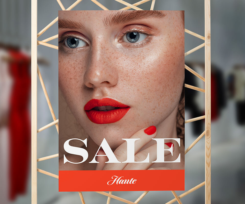 A sale sign that has a large image of a woman with blue eyes, freckles and red lipstick.