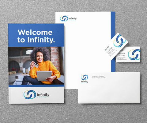 Stationery collection for Infinity Credit Union showing a Welcome folder with a smiling black female holding an ipad, a letterhead, business card and envelope sit to the right.
