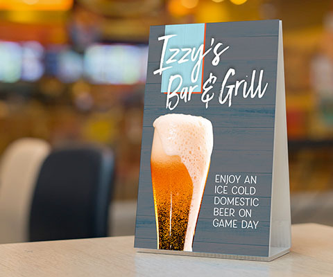 "A gray Izzy's Bar & Grill folded triangular table topper with an image of large beer glass overflowing. The text reads ""Enjoy an ice cold domestic beer on game day."""