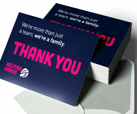 "A stack of blue Thank You cards with white and pink text: ""we're more than just a team, we're a family"" and the helping hands logo."