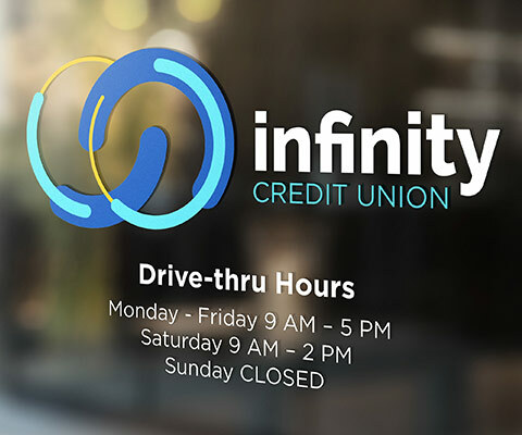 Infinity Credit Union logo showing drive-thru hours on glass